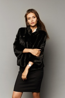 Девушка красивая модель в юбке и шубе, изолированные на студии. зимняя красота с идеальным макияжем в роскошном наряде, изолированном на сером фоне.