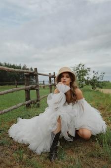 Красивая модельная девушка в модном винтажном платье и соломенной шляпе у молодой невесты в сельской местности в модном ...