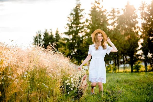 필드, 태양 빛에서 실행되는 흰 드레스에 아름 다운 모델 소녀. 무료 행복한 여자. 따뜻한 색상으로 톤. 선택적 초점.