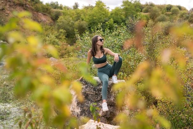 모래 채석장이나 산에 있는 바위 근처에서 포즈를 취하는 아름다운 모델 소녀. 자유