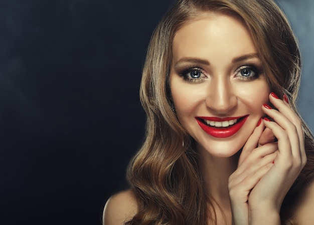 Beautiful model girl with long curly hair and red lips. red manicure on nails. beauty and esthetic care. dark background.