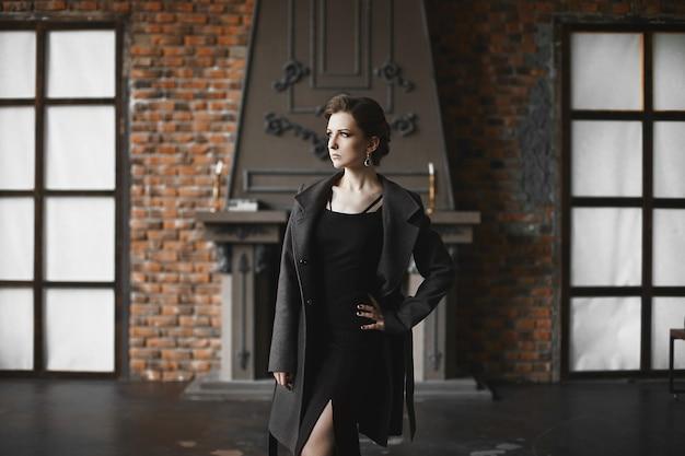 빈티지 인테리어에 포즈 유행 코트에 슬림 바디와 아름 다운 모델 소녀