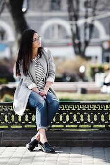 La bellissima modella con gli occhiali si siede sulla staccionata