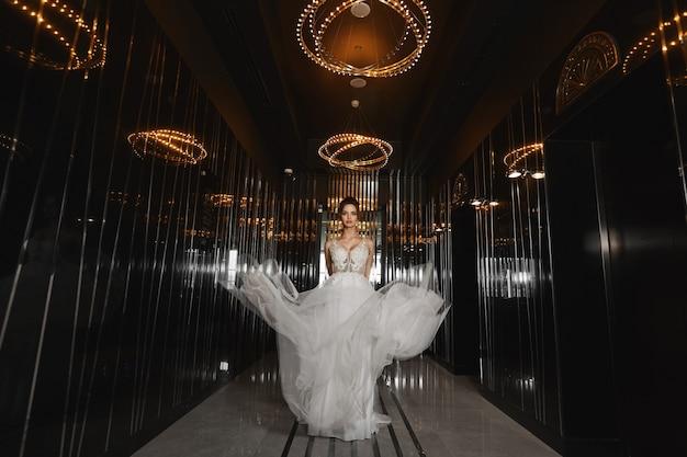 어두운 홀을 걷는 웨딩 드레스의 아름다운 모델
