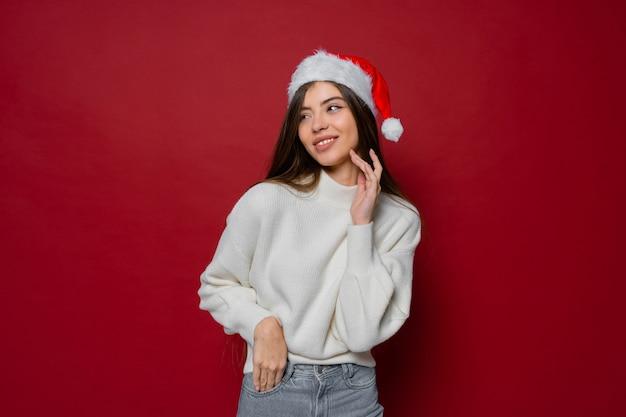 Красивая модель в новогодней шапке и белом уютном свитере позирует на красном