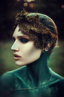 美しいモデルが森の中で自然の精神としてポーズをとっています