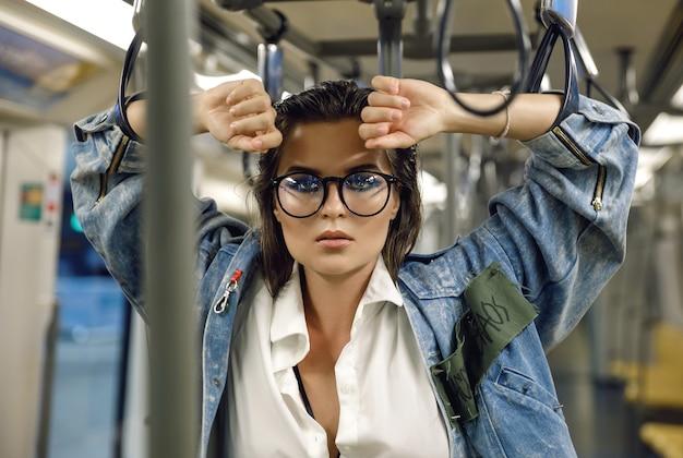아름다운 모델은 지하철 열차의 마차에 포즈