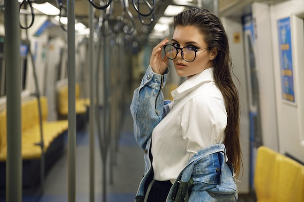 Красивая модель позирует в вагоне поезда метро