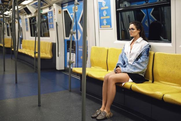 美しいモデルが地下鉄の馬車でポーズをとっている