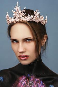 아름다운 모델이 뷰티 촬영을 위해 핑크색 왕관을 쓰고 포즈를 취하고 있습니다.