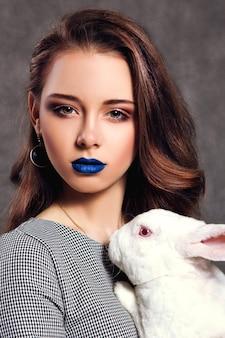 아름다운 모델이 흰 토끼와 함께 포즈를 취하는