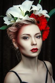 美しいモデルは彼女の顔の周りに創造的な化粧と花でポーズをとっています