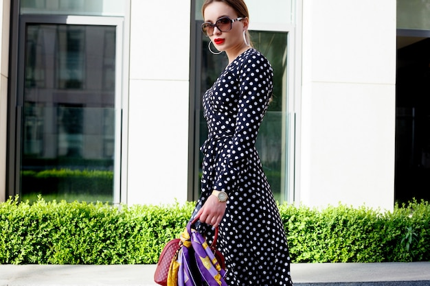 Beautiful model look brunette female wearing white dress with black polka dots is while waking on a city street background with stylish bags in the hand.
