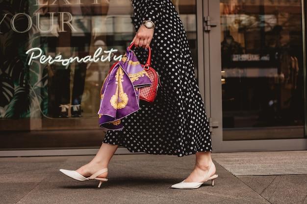 검은 물방울 무늬가 있는 흰색 드레스를 입은 아름다운 모델의 갈색 머리 여성은 세련된 가방을 손에 들고 도시 거리 배경에서 깨어 있는 동안입니다.