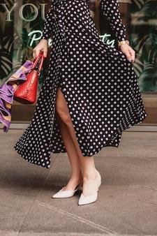 黒の水玉模様の白いドレスを着ている美しいモデルの外観のブルネットの女性は、手にスタイリッシュなバッグを持って街の通りの背景に目覚めている間です。