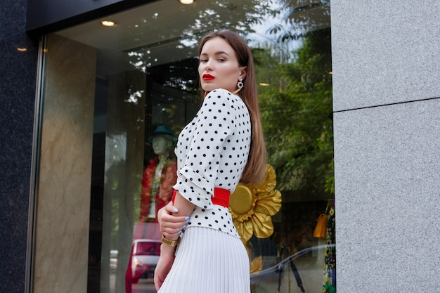 Красивая модель выглядит брюнетка женщина в белом платье с черными точками в горошек во время пробуждения на фоне городской улицы со стильными сумками в руке.