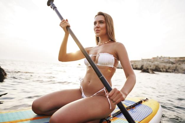 깨끗한 물로 바다에서 휴식을 취하는 아름다운 모델 패들보딩