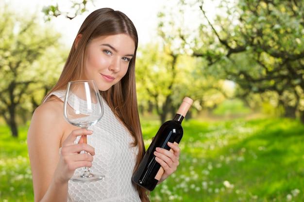 Beautiful model portrait isolated over studio background holding wine glass