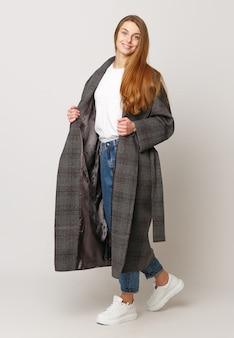 白い背景の上の茶色の長いコートでポーズをとる美しいモデル。スタジオショット。衣料品の広告コンセプト。