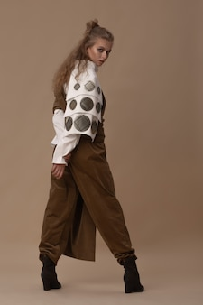 흰색면 블라우스와 카키색 바지를 입은 아름다운 모델