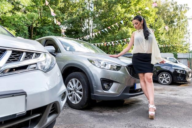Красивая модель позирует возле новой машины на стоянке