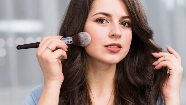 Beautiful model posing with powder brush
