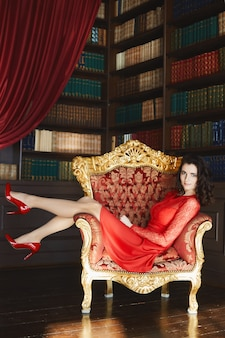 Beautiful model in red stylish dress and red shoes sits on the gold vintage armchair in the interior