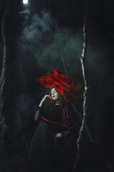 Beautiful model rose hat  is posing in a dark