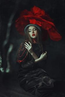 아름다운 모델 장미 모자는 어두운 스튜디오에서 포즈입니다