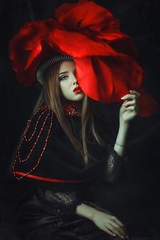 美しいモデルのローズハットは暗いスタジオでポーズをとってください。