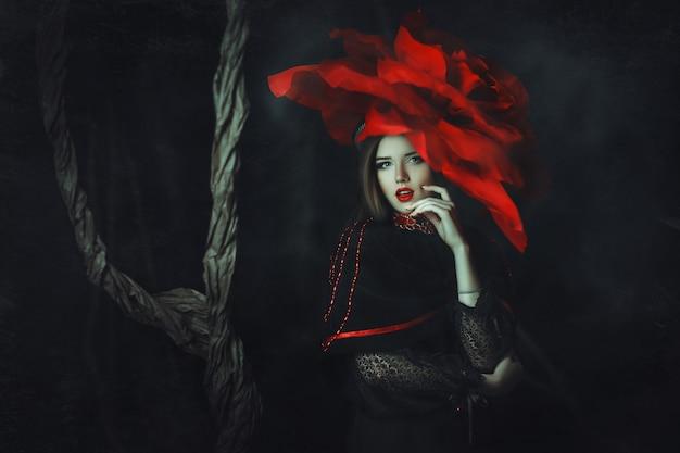 아름 다운 모델 장미 모자는 어둠 속에서 포즈