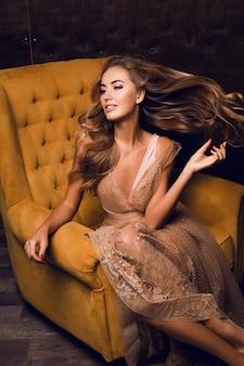 肘掛け椅子に座って、髪を振って美しいモデル