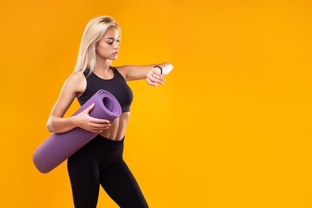 A beautiful model in sportswear with a smart watch and a mat in her hands on a yellow background