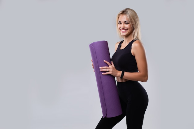 A beautiful model in sportswear with a smart watch and a mat in her handson a gray background