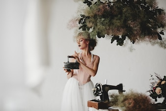 Beautiful model stands with an old iron among beautiful bouquets in the room
