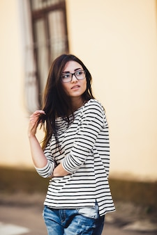 Bellissimo modello in un maglione a righe con gli occhiali