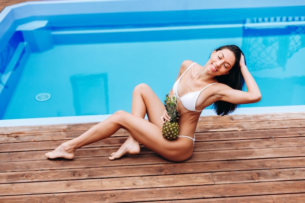 Beautiful model in swimsuit posing near the pool