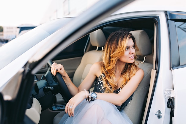 Beautiful model in tulle skirt driving a car. she is looking to side.