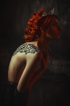Beautiful model wearing creative body art and crown