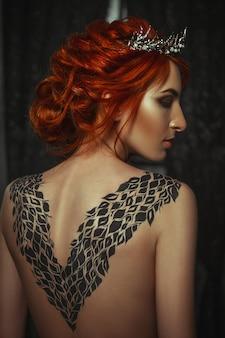 創造的なボディーアートドレスを着ている美しいモデルは暗いスタジオでポーズをとってください。