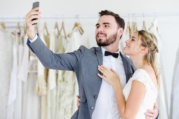 Красивая модель свадебная пара, проведение смарт-телефон онлайн видео-вызов, глядя на экран