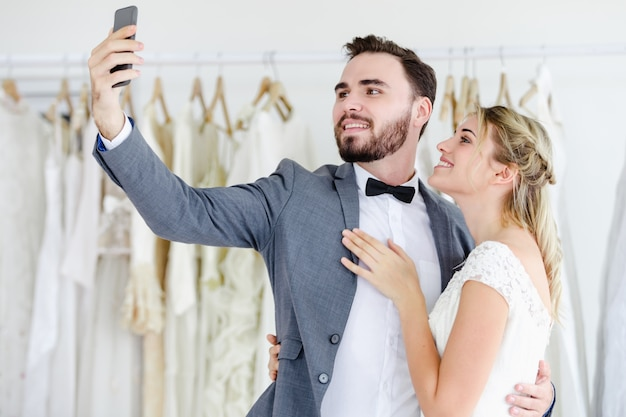 Beautiful model wedding couple holding smart phone online video call looking at screen