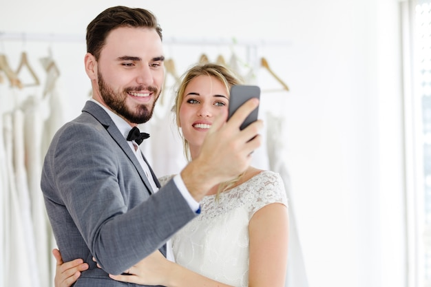 Beautiful model wedding couple holding smartphone online video call looking at screen