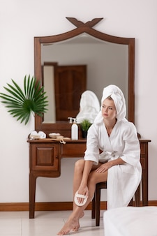 A beautiful model in a white coat and white towel on her head rubs her legs with a scrubbing brush