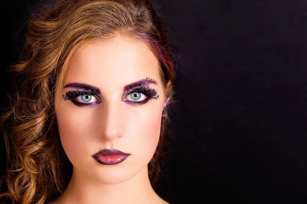 검은 배경에 패션 메이크업과 헤어 스타일을 가진 아름다운 모델