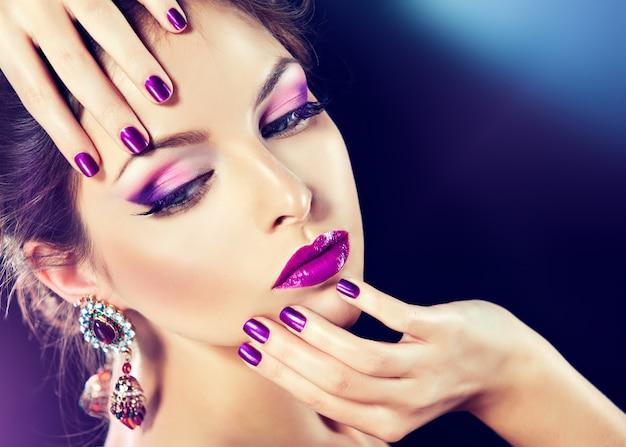 優雅な指の爪にファッショナブルなメイクとパープルのマニキュアを施した美しいモデル。紫色のまぶたと唇の明るいイブニングメイク。