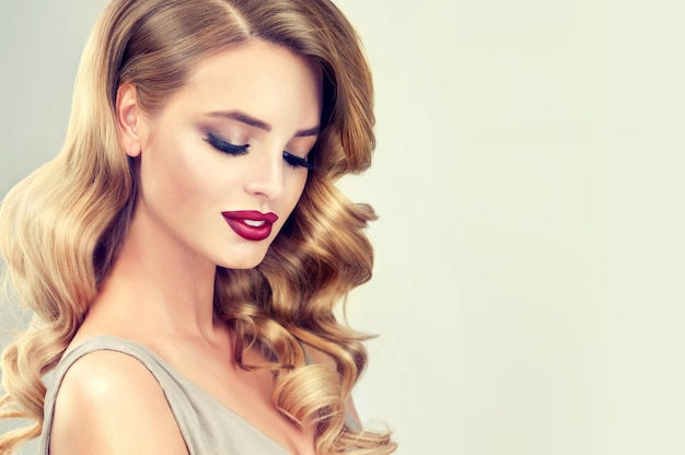 Beautiful model with long, dense, curly  evening hairstyle and vivid makeup with long black eyelashes and red lipstick. hairdressing art, hair care and beauty products.