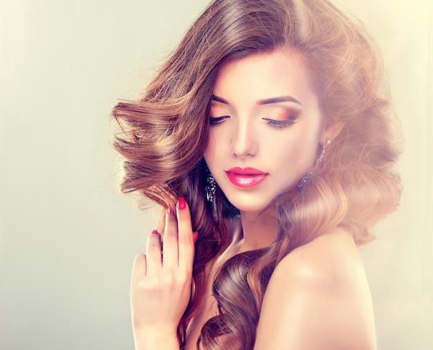 長くて濃い巻き毛と赤い口紅の鮮やかなメイクの美しいモデル。理髪アート、ヘアケア、美容製品。