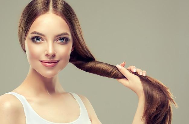 Красивая модель с длинными, густыми, прямыми волосами и ярким макияжем держит в пальмовом хвосте ухоженные и здоровые волосы.
