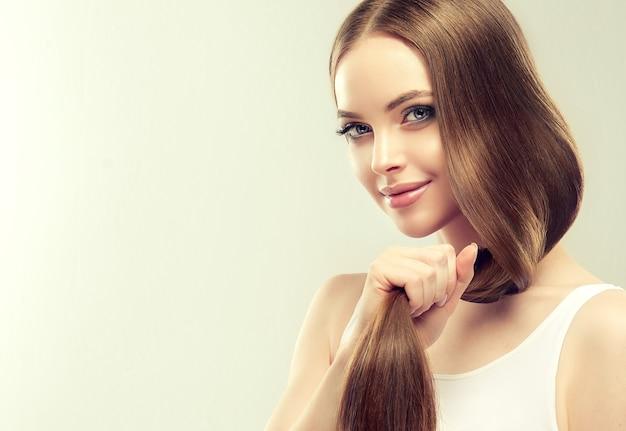 長くて濃いストレートヘアと鮮やかなメイクの美しいモデルが、手入れの行き届いた健康な髪の手のひらの尻尾を支えています。